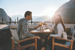 Two people seated with mountain views at Rundle Lounge, one of the best patios in Banff