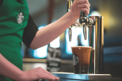 Starbucks barista pours coffee from tap. They also have one of the best patios in Banff