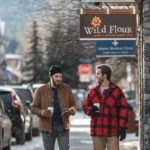 Two men walk down Bear Street under the sign for Wild Flour Bakery, one of Banff's safe spaces