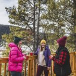 Three friends drink warm drinks on the patio overlooking backcountry scenery at Mount Engadine Lodge